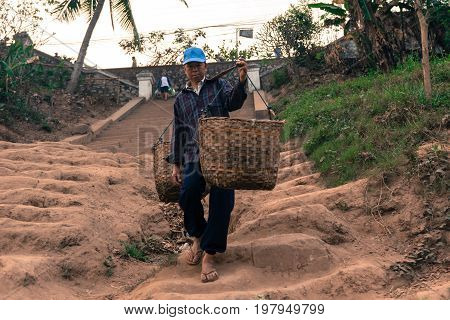 LUANG PRABANG LAOS - MARCH 12 2017: Horizontal picture of Local lao man down the stairs with a basket in Mekong's River in Luang Prabang Laos.