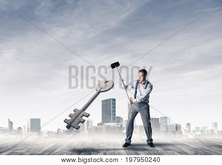 Determined businessman against cityscape breaking with hammer stone key figure