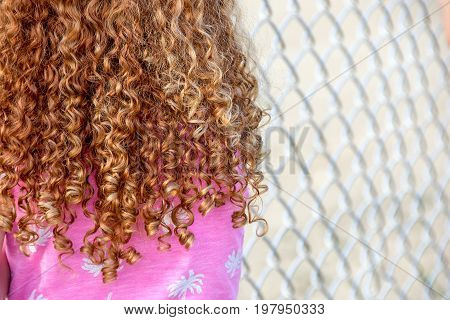 young girl with curly red hair by chain link fence