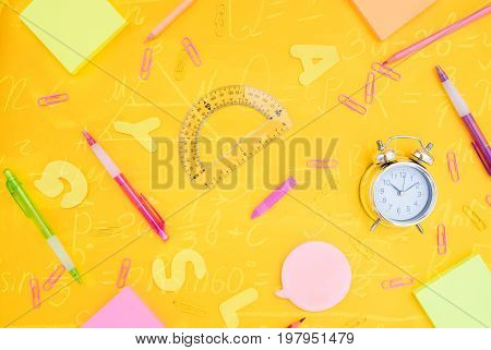 back to school or office styed pattern with multicolored school supplies on yellow back ground with math formulas