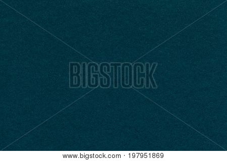Texture of old dark green blue paper closeup. Structure of a dense cardboard. The emerald background.