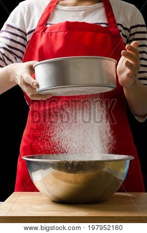 Woman sifting wheat flour into a bowl for cooking in the kitchen,Homemade bakery