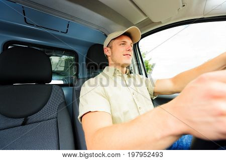 A uniformed messenger is driving his delivery van