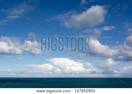 Clouds Against Blue Skies Above The Ocean