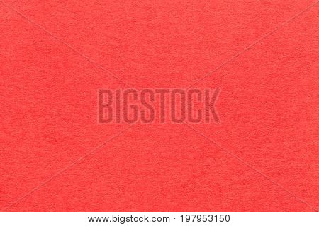 Texture of old bright red paper closeup. Structure of a dense cardboard. The carmine background.