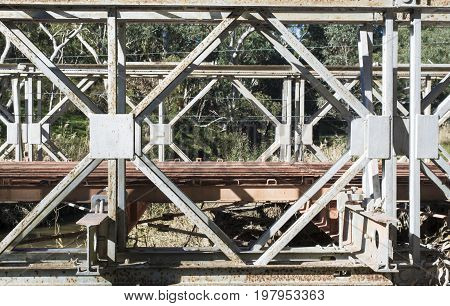 Abstract view of an old disused and partially dismantled bridge constructed with heavy duty metal frame that is now rusting.