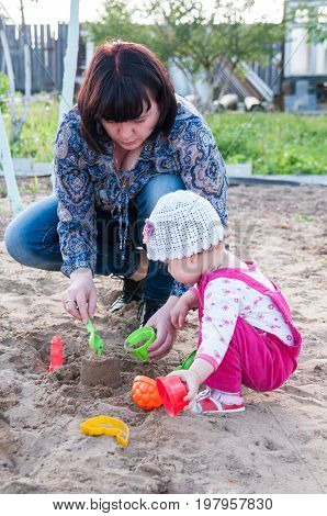 Brunette Mom Playing With Her Baby In The Sandbox