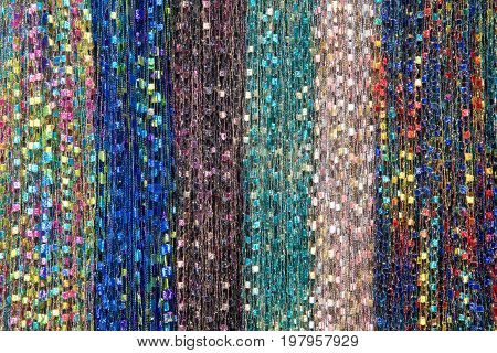 Background fabric strings creating scarfs multiple colored scarves hanging in rows.. Blue green brown rainbow pink yellow. Hanging vertically