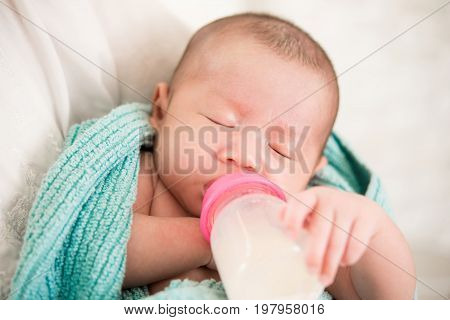 Sleepy cute newborn baby drinking milk from bottle in mother arms