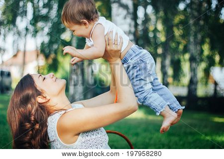 Happy loving mother and her baby child playing outdoors in the park
