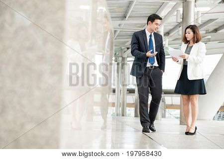 Asian businessman and secretary walking and discussing work in outdoor covered walkway