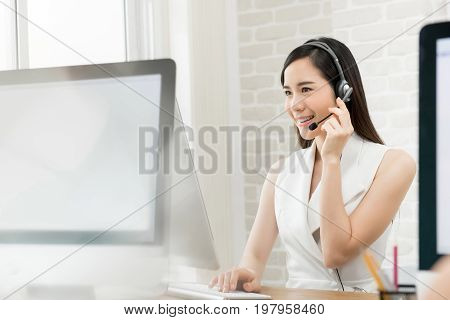 Beautiful Asian business woman wearing microphone headset working in the office as a telemarketing customer service agent call center job concept