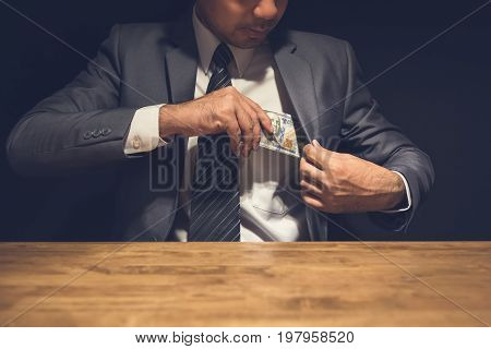 Dishonest businessman putting money US dollars into his suit pocket in the dark - corruption and embezzlement concepts