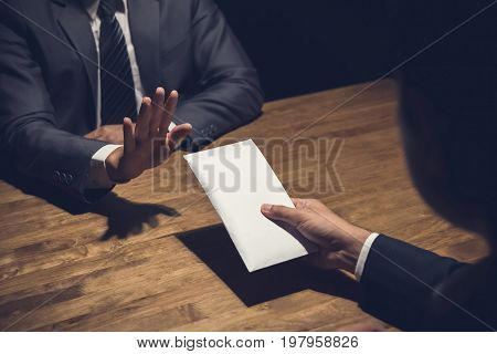 Businessman rejecting money in white envelope offered by his partner in the dark - anti bribery concept
