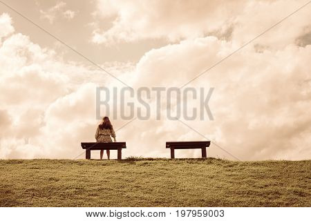 a women sitting alone on a bench waiting for love alone concept