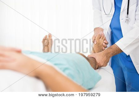 Doctor examining and training broken leg patient in hospital - physical therapy concept