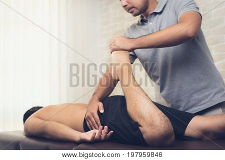 Physical therapist stretching leg of sportsman patient in clinic