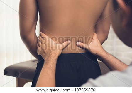 Therapist giving massage to back pain patient in clinic - physical therapy concept