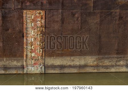 Depth Marker Printed Onto The Side Of Old Cargo Ship