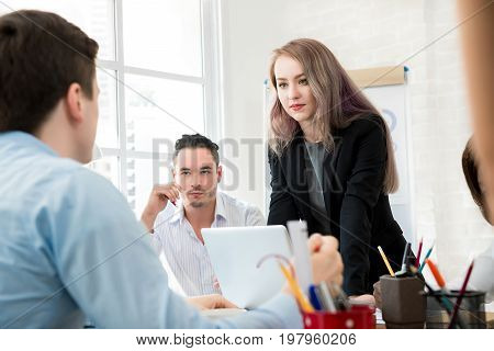Female leader standing and paying attention to her colleague in the meeting