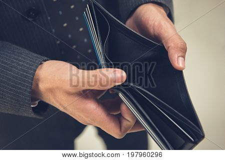 Broke businessman opening empty wallet showing he has no money