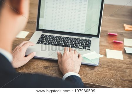 Businessman concentrating on using laptop computer analysing data on screen - over shoulder view
