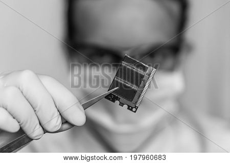 Scientist Holding And Examining Damaged Electrical Component