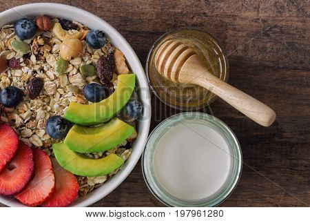 Muesli or granola on white bowl with fresh fruits nuts and cereal. Granola top with blueberries strawberries and avocado served with milk and honey for breakfast.Granola is healthy food for dieting.Muesli or granola in top view or flat lay.