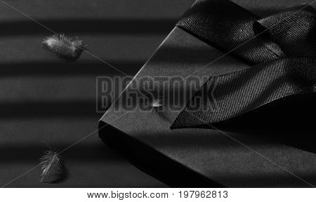 Black gift box on a dark contrasted background decorated with a textured bow and feathers creating a romantic atmosphere. Typically used for birthday anniversary presents gift cards post cards letters.