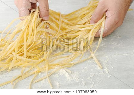 Men's hands hold a raw homemade noodles on a white background close up