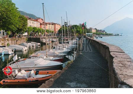June 13th, 2017 - Lombardy, Italy. Coastline of Bellano fishing village, situated on Como Lake shore. Traditional italian houses, boats in port and embankment in small coast town Bellano.