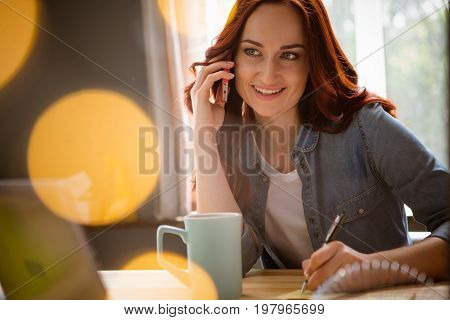 CLose up portait of foxy freelancer woman talking on phone. Home office concept, girl at working space. Toned image with sun beams.