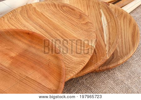 The wooden plates are handmade at the fair, prepared for sale. Wooden plates have a beautiful texture. Various wooden utensils in retro style. The dishes sold at the fair.