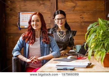 Brunette ladyboss and ginger freelancer woman at working place. Working team at home office. Toned image.