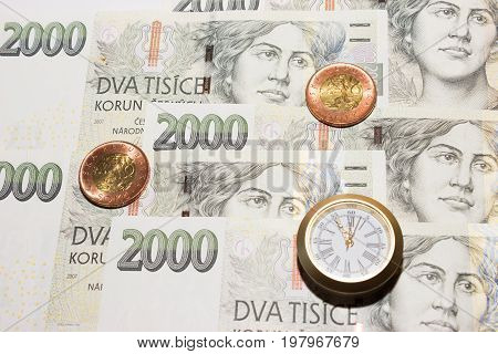 Czech banknotes like background and at the front are coins and a clock that have five to twelve time. Highest time for action.