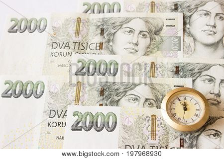 Czech banknotes like background and at the front are clocks that have five to twelve time. Highest time for action.