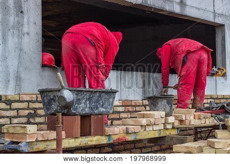 Two Mason Bricklaying Outdoors
