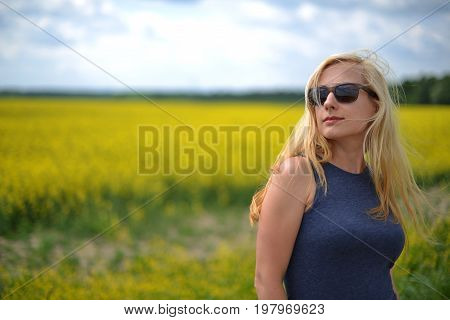 Young and pretty woman at field of canola