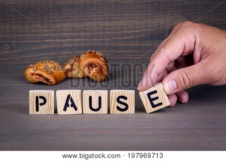 pause. Wooden letters on dark background. Office desk