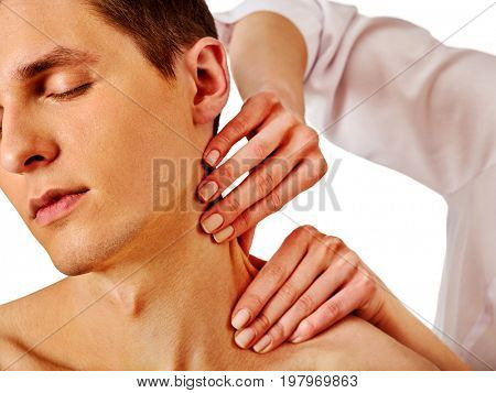 Shoulder and neck massage for man in spa salon. Doctor making therapy in rehabilitation center. Folded towels in the background. Massage the neck in an elite spa salon.