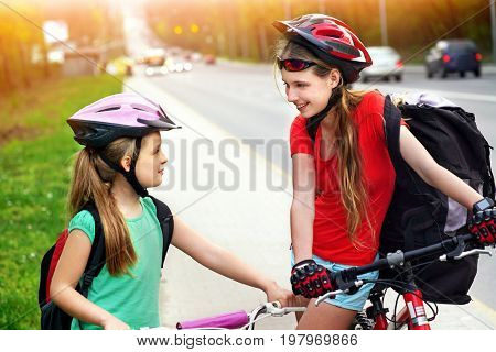 Bikes bicyclist girl. Girls wearing bicycle helmet and glass with rucksack ciclyng bicycle. Girls children cycling on yellow bike lane. Color tone on shiny sunlight background. There are cars on road.
