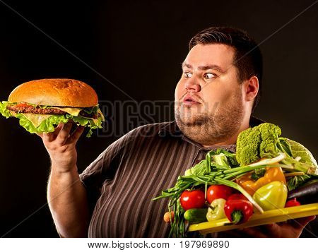 Diet fat man who makes choice between healthy and unhealthy food. Overweight male with hamburgers. Choice between healthy harmful nutrition.