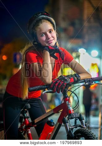 Bikes bicyclist girl. Girls wearing bicycle helmet. Night city street. Burning shop windows in the background.