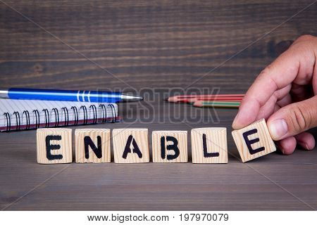 Enable. Wooden letters on dark background. Office desk