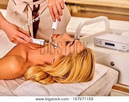Facial massage at beauty salon. Electric stimulation skin care of woman. Equipment for microcurrent lift face. Anti aging face and neck rejuvenation and non surgical treatment indoor.