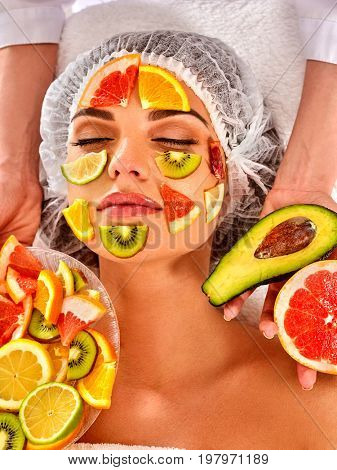 Facial mask from fresh fruits for woman. Beautician apply slices of avocado, grapefruit and kiwi Girl in medical hat lying on spa bed for skin care procedure in salon. Mask against sagging skin.