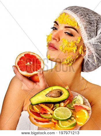 Facial mask from fresh fruits for woman. Girl in medical hat bit slices of kiwi and hold plate with fruit salad. Mask against sagging skin. Traditional medicine has been widely used.