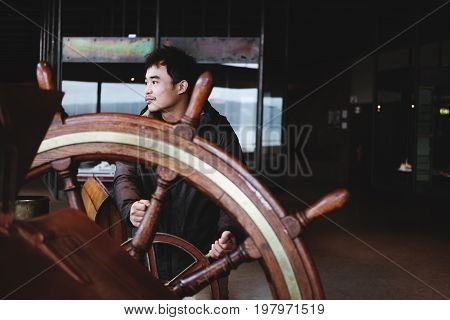 a man controlling wooden helm, in old ship