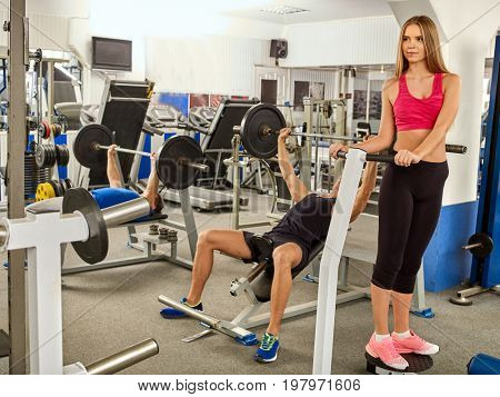 Fitness friends workout gym. Man working on bench press. He lifting barbell. Girl while taking exercises. Group work people on treadmill background. Girl wants to keep herself in good shape.
