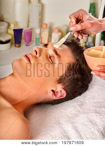 Mud facial mask of man in spa salon. Massage with clay full face. Guy on with therapy room. Man lying wooden spa bed. Rejuvenating rest in the elite spa salon. Anti-aging cosmetic mask.
